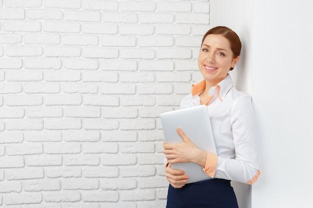 Portrait d'une femme d'affaires jeune utilisant un ordinateur portable au bureau