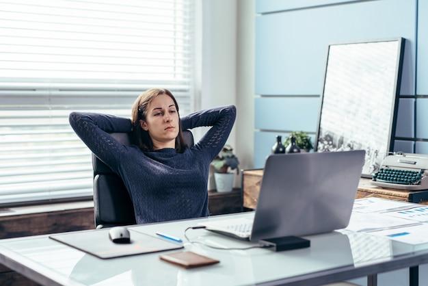 Portrait de femme d'affaires avec les mains derrière la tête.
