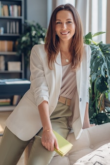 Portrait d'une femme d'affaires à la maison avec un livre.