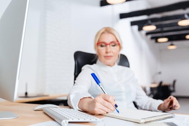 Portrait d'une femme d'affaires mature attrayante souriante écrit dans un ordinateur portable au bureau