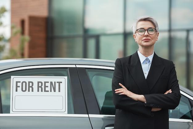 Portrait de femme d'affaires mature en costume noir debout avec les bras croisés. elle suggère la voiture à louer