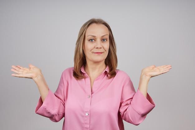 Portrait d'une femme d'affaires mature dans un chemisier rose tenant ses mains
