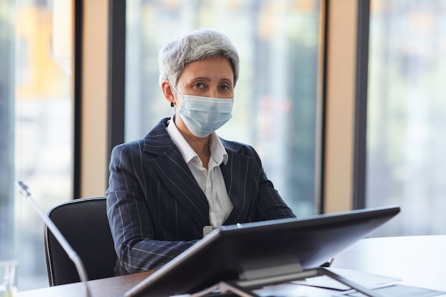 Portrait de femme d'affaires mature en masque de protection assis à la table avec ordinateur et regardant office