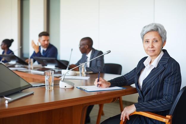 Portrait de femme d'affaires mature à la recherche alors qu'il était assis à la conférence avec ses collègues