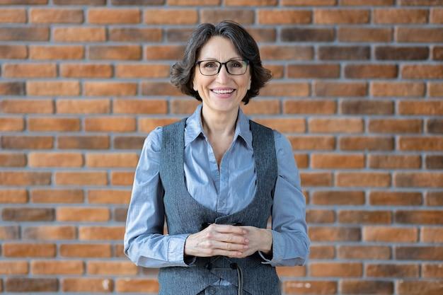 Portrait d'une femme d'affaires mature souriante portant des lunettes dans le contexte d'un mur de briques au bureau