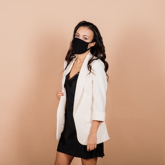 Portrait de femme d'affaires noire portant un masque facial pendant l'épidémie de virus dans un studio.