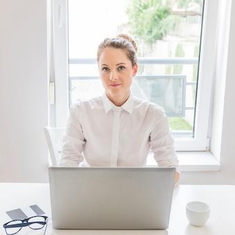 Portrait de femme d'affaires avec un ordinateur portable assis devant la fenêtre