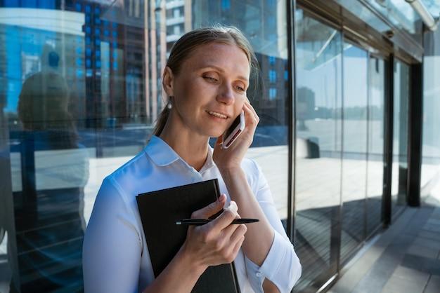 Portrait d'une femme d'affaires parlant au téléphone devant un immeuble de bureaux