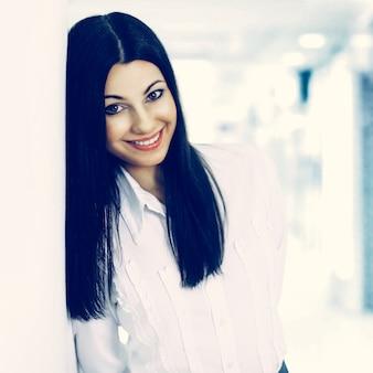 Portrait d'une femme d'affaires prospère sur l'arrière-plan lumineux