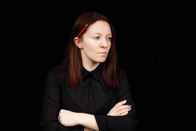 Portrait de femme d'affaires prospère dans une chemise noire avec les mains croisées sur fond noir.