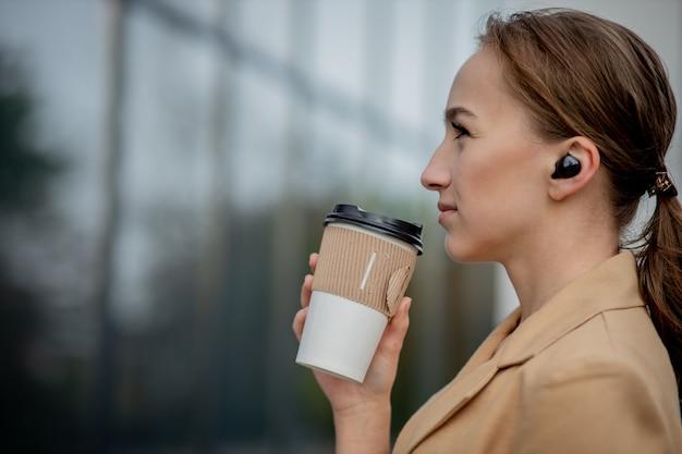 Portrait de femme d'affaires prospère tenant une tasse de boisson chaude dans la main sur sa façon de travailler sur la rue de la ville