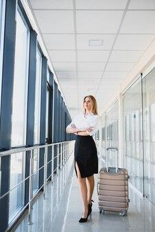 Portrait de femme d'affaires prospère voyageant avec cas à l'aéroport