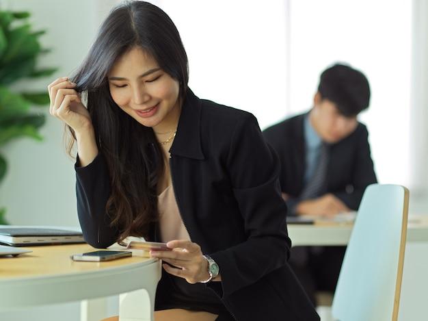 Portrait de femme d'affaires à la recherche sur la carte de crédit dans sa main tout en payant en ligne sur smartphone
