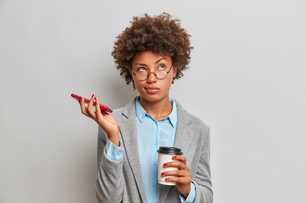 Portrait de femme d'affaires réfléchie avec des cheveux afro a ennuyé l'expression attend l'appel est titulaire d'un téléphone mobile