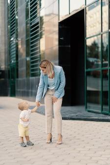 Portrait d'une femme d'affaires réussie en costume bleu avec bébé
