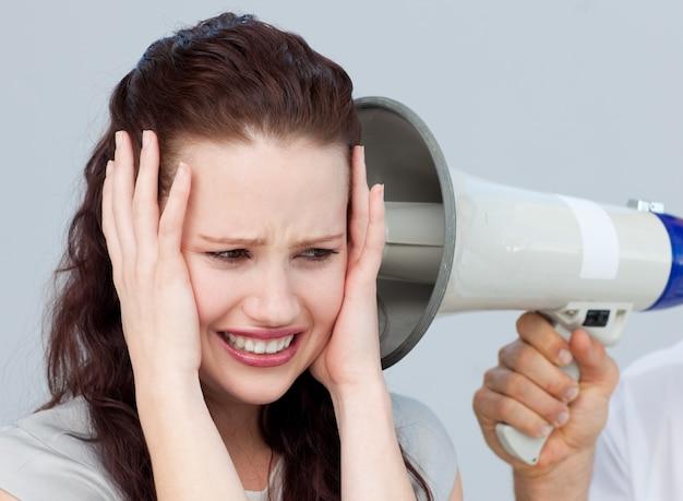 Portrait d'une femme d'affaires s'énerver avec un mégaphone