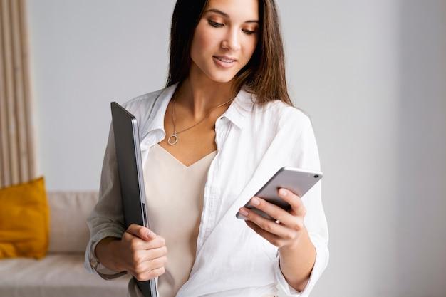 Portrait d'une femme d'affaires, se dresse et tient un smartphone dans ses mains.
