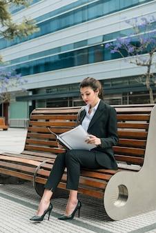 Portrait, femme affaires, séance, banc, lecture, dossier