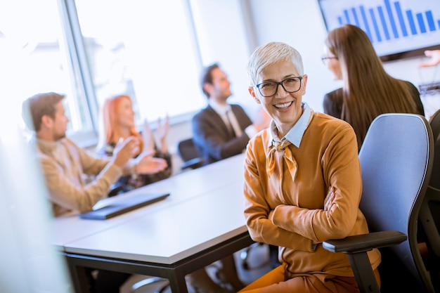 Portrait de femme d'affaires senior gai au bureau