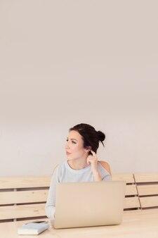 Portrait d'une femme d'affaires sérieuse utilisant un ordinateur portable au bureau. belle femme élégante prenant des notes au café