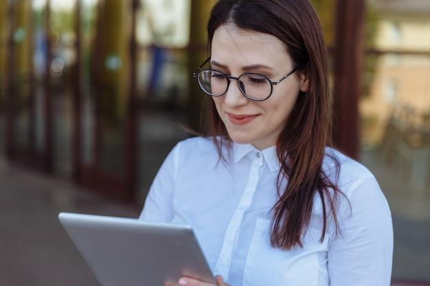 Portrait de femme d'affaires souriant à l'aide de tablet pc en face de l'immeuble de bureaux.