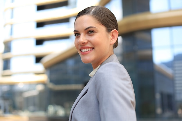 Portrait d'une femme d'affaires souriante élégante dans des vêtements à la mode dans la grande ville en détournant délibérément les yeux.