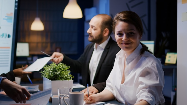 Portrait d'une femme d'affaires souriante regardant dans la caméra faisant des heures supplémentaires dans la salle de réunion d'une entreprise commerciale tard dans la nuit. travail d'équipe multiethnique divers de bourreaux de travail discutant de la stratégie d'investissement