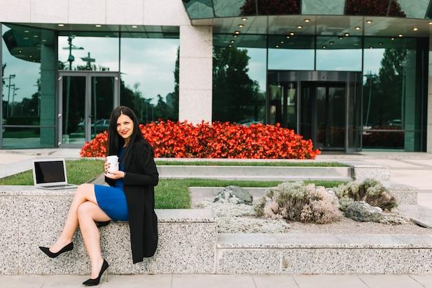 Portrait d'une femme d'affaires avec une tasse de disposition et un ordinateur portable assis à l'extérieur du bâtiment de bureau