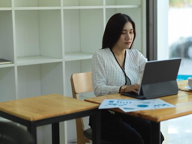 Portrait de femme d'affaires travaillant avec tablette numérique et document commercial sur table en bois