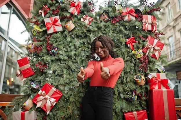 Portrait d'une femme africaine aux cheveux bouclés portant un col roulé rouge à la mode posant contre des décorations de noël, thème du nouvel an. montrez les pouces vers le haut.