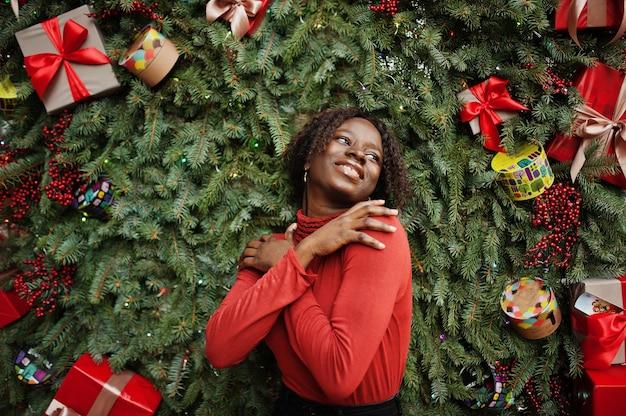Portrait d'une femme africaine aux cheveux bouclés portant un col roulé rouge à la mode posant contre des décorations de noël, thème du nouvel an.