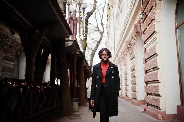 Portrait d'une femme africaine aux cheveux bouclés portant un manteau noir à la mode et un col roulé rouge marchant en plein air.