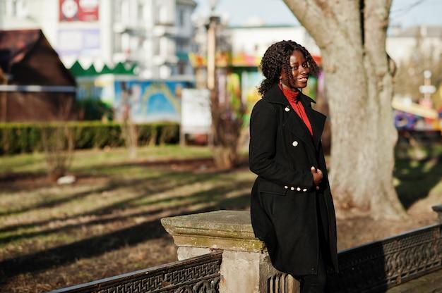 Portrait d'une femme africaine aux cheveux bouclés portant un manteau noir à la mode et un col roulé rouge posant en plein air par une journée ensoleillée.
