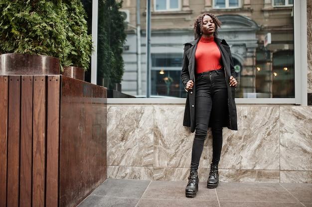 Portrait d'une femme africaine aux cheveux bouclés portant un manteau noir à la mode et un col roulé rouge posant en plein air.