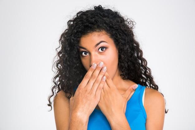 Portrait d'une femme africaine couvrant sa bouche isolée