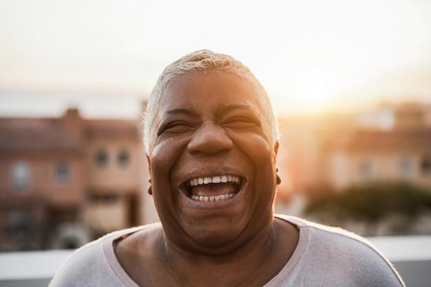 Portrait de femme africaine senior heureuse souriant en plein air dans la ville - focus sur le visage