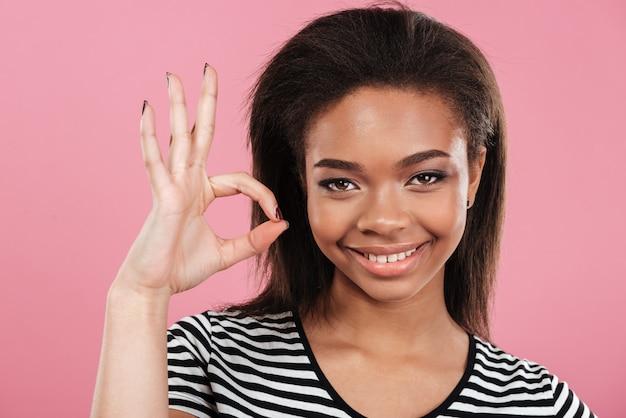 Portrait d'une femme africaine souriante satisfaite montrant le geste ok