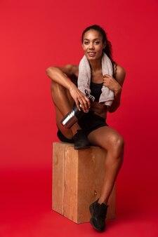 Portrait de femme afro-américaine athlétique en sportswear noir assis sur une boîte avec une serviette et une bouteille d'eau, isolé sur mur rouge