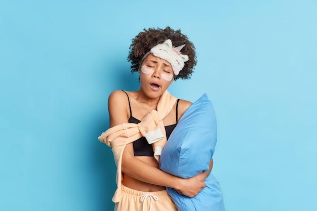 Portrait de femme afro-américaine aux cheveux bouclés endormie bâille après le réveil précoce tient oreiller habillé en pyjama et masque de sommeil incline la tête applique des tampons de collagène sous les yeux isolés sur mur bleu
