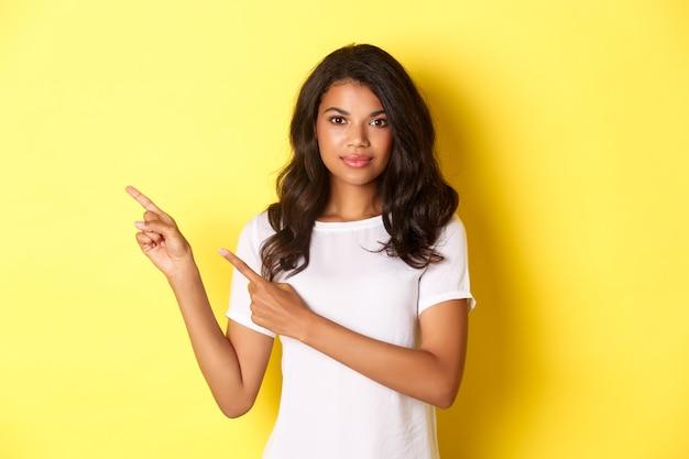 Portrait d'une femme afro-américaine belle et confiante, pointant les doigts vers la gauche