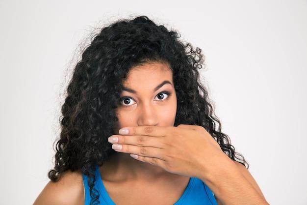 Portrait d'une femme afro-américaine couvrant sa bouche isolée