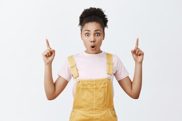 Portrait de femme afro-américaine créative et élégante impressionnée et surprise en salopette jaune, plier les lèvres et pointant vers le haut