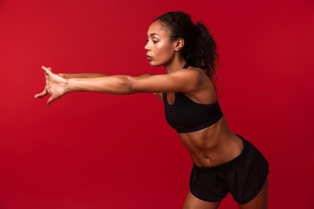 Portrait de femme afro-américaine féminine en vêtements de sport noir qui s'étend de son corps, isolé sur mur rouge