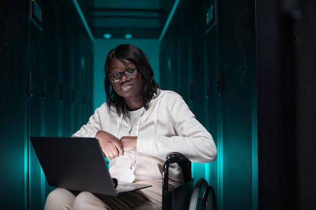 Portrait d'une femme afro-américaine handicapée utilisant un ordinateur portable et regardant la caméra tout en travaillant dans la salle des serveurs, opportunité d'emploi accessible, espace de copie