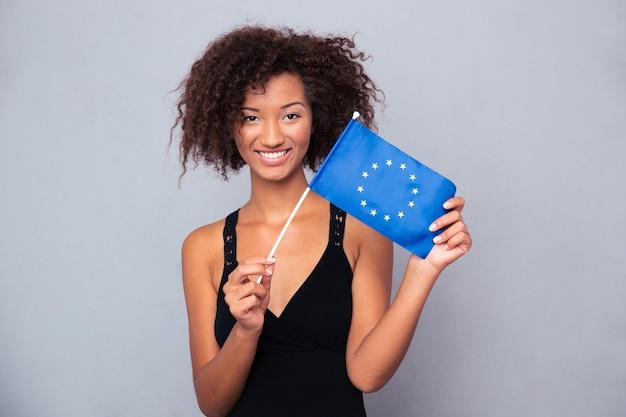Portrait d'une femme afro-américaine heureuse tenant le drapeau de l'euro sur un mur gris et regardant à l'avant