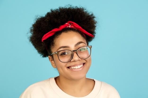 Portrait de femme afro-américaine isolé sur un mur bleu avec copyspace