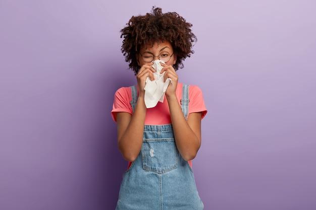 Portrait de femme afro-américaine malade éternue dans un tissu blanc, souffre de rhinite et de nez qui coule