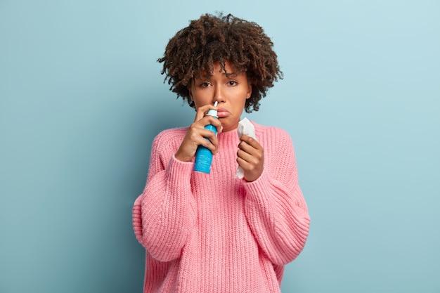 Portrait d'une femme afro-américaine mécontente renifle un aérosol nasal, se sent malade, a le nez qui coule, utilise des médicaments pour le nez bouché, tient des tissus, a une expression faciale triste, porte un pull rose.
