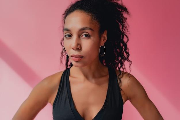 Portrait de femme afro-américaine noire en tenue de fitness haut noir sur rose