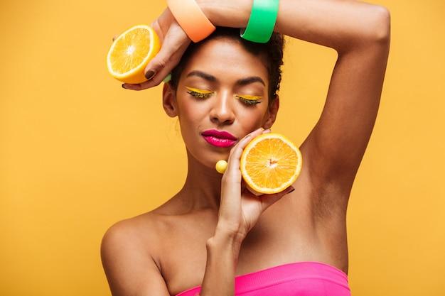 Portrait de femme afro-américaine sensuelle avec les yeux fermés tenant deux parties d'orange à la caméra en appréciant les agrumes isolés, sur le mur jaune